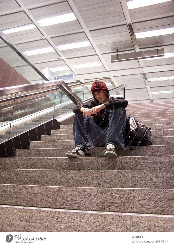 Gedankenversunken2 Stil Mensch Mann Erwachsene Jugendliche Flughafen Treppe Rolltreppe Mütze sitzen träumen warten Einsamkeit abgesondert leer Baseballmütze