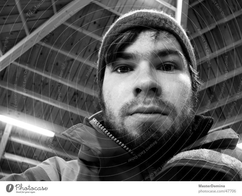Verwirrung Porträt maskulin Mann Bart Lippen Vollbart Mütze Wollmütze Jacke Holzdach Lampe Trägheit erstaunt Überraschung unklar Innenaufnahme Typ Gesicht Auge