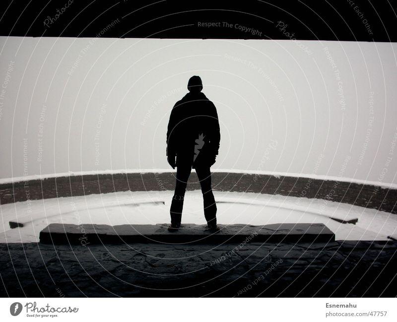 Der Mann in Schwarz dunkel schwarz weiß grau hell Licht Nebel kalt Winter Mauer rund Mütze Jacke Hose Schuhe Schnee Baseballmütze Stein Schatten Fluss