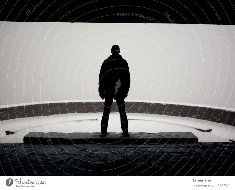 Der Mann in Schwarz weiß Winter dunkel schwarz kalt Schnee Mauer grau Stein hell Nebel Schuhe rund Fluss Hose
