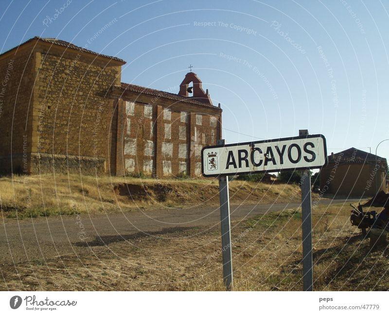 Arcayos Spanien Ausland Süden Friedhof Kirchplatz Straßennamenschild Landstraße Fahrbahn Außenaufnahme rot braun beige Physik Sommer trist Einsamkeit