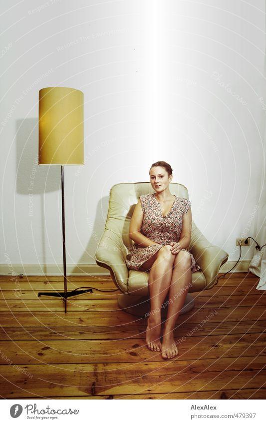 Junge, barfüßige Frau in einem Sommerkleid sitzt in beigem Sessel Junge Frau Jugendliche Beine Fuß 18-30 Jahre Erwachsene Kammer Dielenboden Stehlampe Steckdose