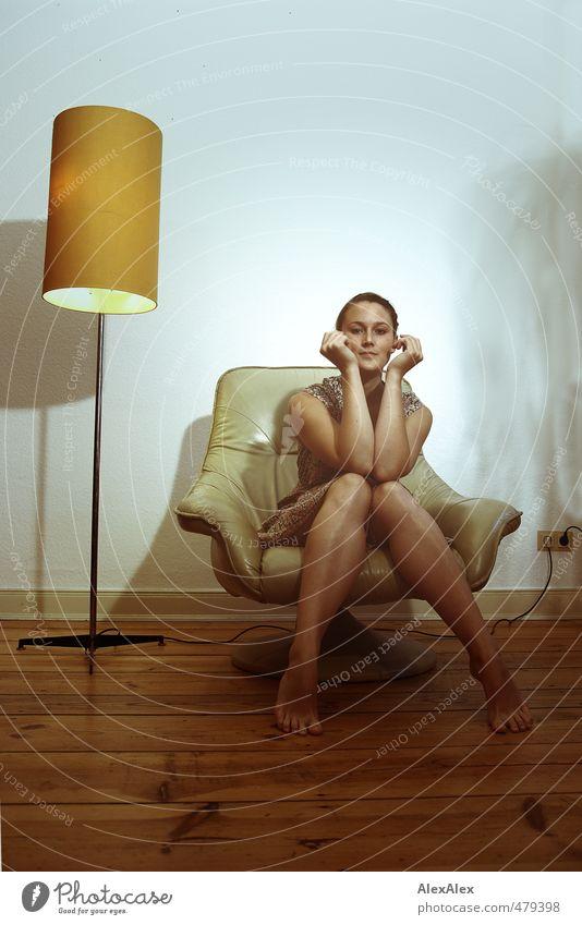 Junge Frau in Kleid sitzt barfuß auf einem Sessel und hält die Arme zum Gesicht Stehlampe Jugendliche Beine Gesichtsausdruck 18-30 Jahre Erwachsene Sommerkleid