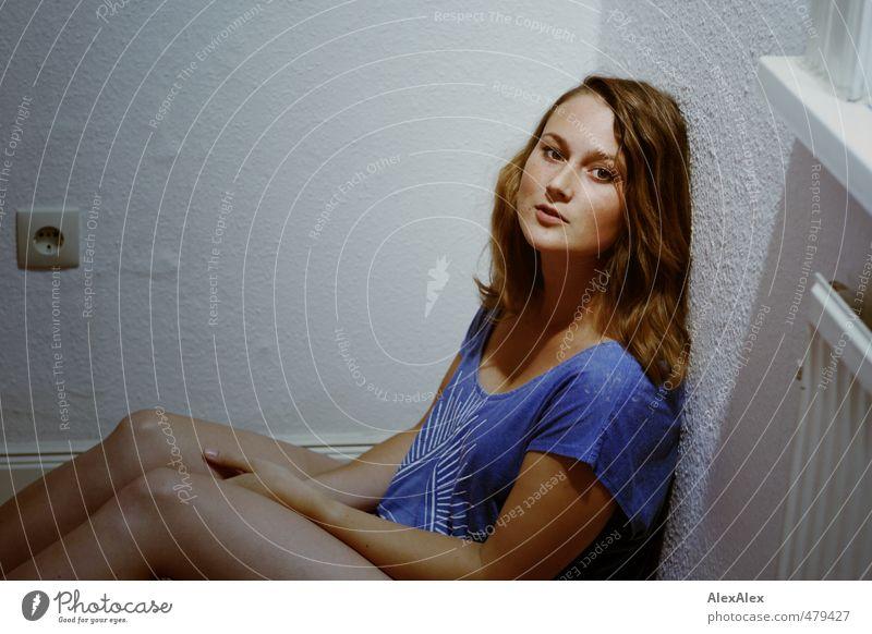 Junger Frau sitzt in einer Zimmerecke und schaut hoch Junge Frau Jugendliche Knie Beine 18-30 Jahre Erwachsene T-Shirt brünett langhaarig Steckdose Heizung