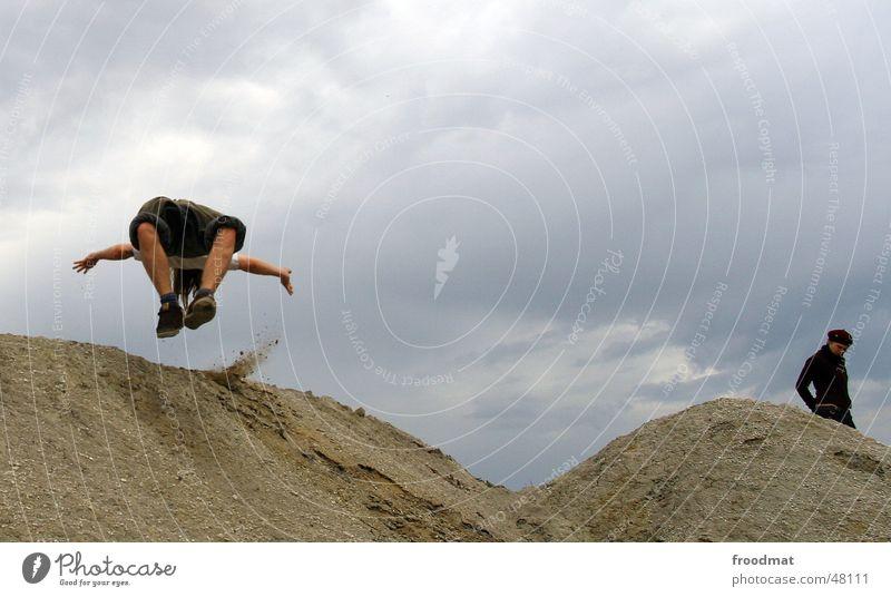 Salto Mann Frau springen Aktion grau schlechtes Wetter man woman Bergbau Sand Wüste Regen Wolken fliegen Bewegung Dynamik Konstruktion