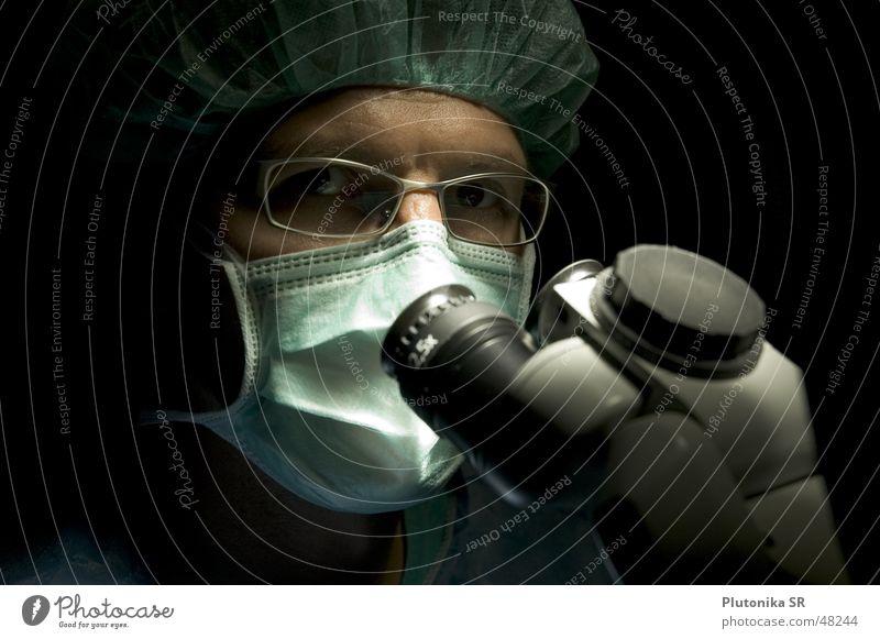 Dr. in the Dark Gesundheitswesen Arzt Brille Mikroskop dunkel Mundschutz Farbfoto Innenaufnahme Detailaufnahme Textfreiraum links Textfreiraum oben