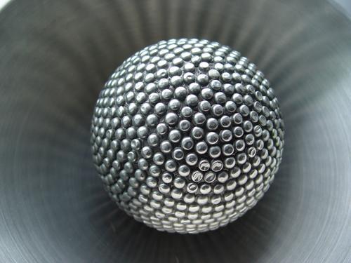 Metallkugel, die das Licht in einer Metallschüssel reflektiert. Noppe Massage grau Stahl Edelstahl glänzend Kugel Ball Silber kugelrund Objektfotografie