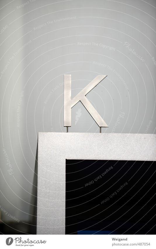 K-Frage Haus schwarz Ferne grau Fassade Schilder & Markierungen Schriftzeichen Hinweisschild Zeichen Buchstaben hängen Eingang silber Warnschild