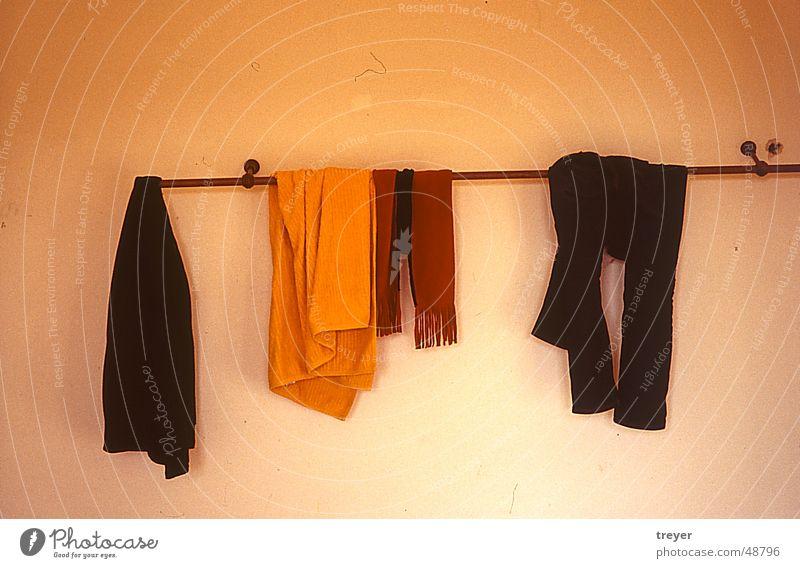 Kleider auf Kleiderstange weiß rot schwarz gelb Wand braun orange Bekleidung Hose Hemd Schal Stab Handtuch Kleiderständer