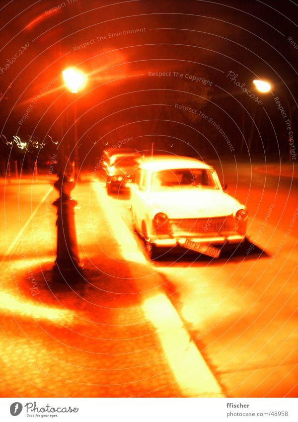 Roter Trabbi Lampe Licht Laterne rot gelb weiß Nacht Osten Nummernschild kaputt Bürgersteig Sozialismus orange Ampel alt DDR klapprig Straße PKW Rad Metall
