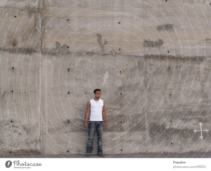 The Wall Mensch Mann weiß Wand Stein Mauer klein Beton groß Jeanshose Pfeil Loch