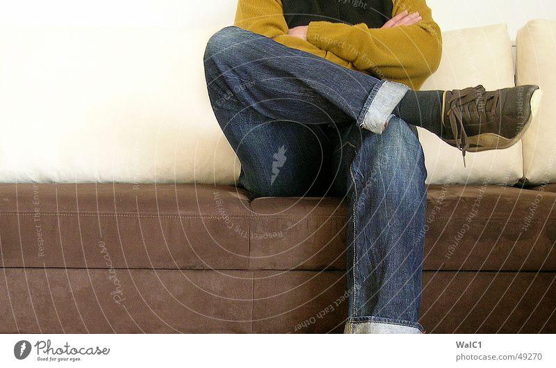 Sitz 02! Mann Pullover Weste Hand Sofa Warteraum Schuhe Puma retro sitzen warten Jeanshose Detailaufnahme Turnschuh