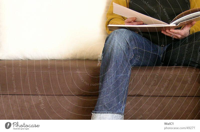 Sitz 03! Mann Pullover Weste Hand Sofa Warteraum Schuhe Puma retro Buch lesen Blatt sitzen warten Jeanshose Detailaufnahme Turnschuh album