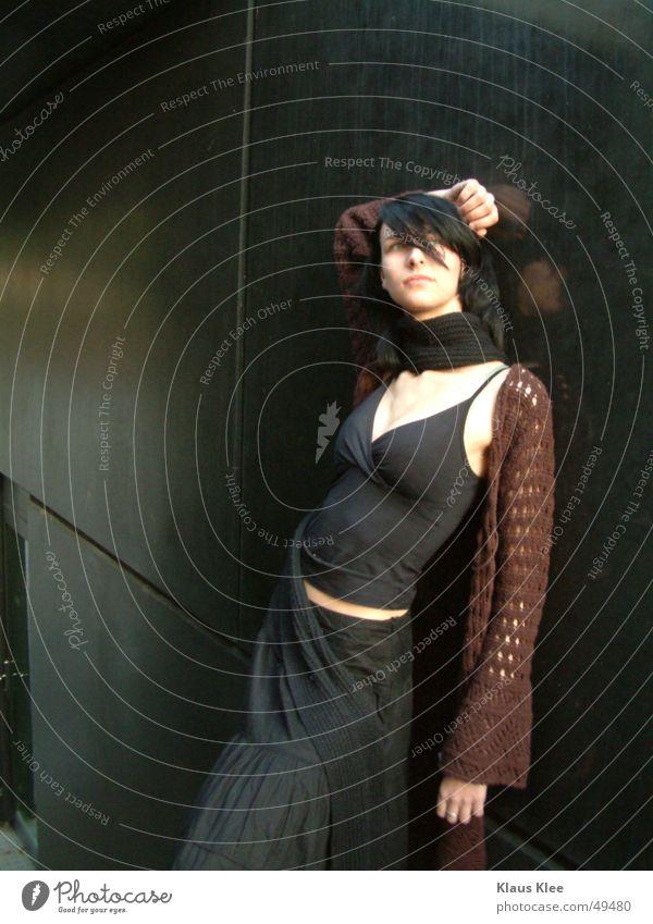 Kiako Frau Außenaufnahme Porträt Beton schwarz braun Top Abenddämmerung Schal Streifen Muster schön genießen anlehnen Schulter Gebäude Hand Stein Bauch Arme Tür