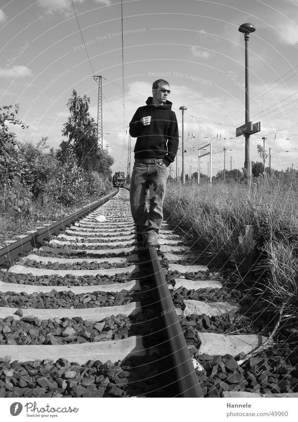 railway-walker Eisenbahn Mann maskulin Gleise Außenaufnahme Sonnenbrille schwarz weiß Wiese Körperhaltung Pullover Bahnhof Coolness Himmel Jeanshose