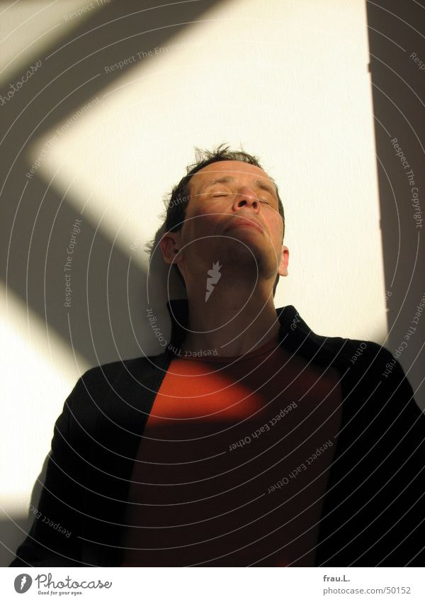 im Sonnenlicht sitzen Mann Winter Gesicht ruhig schwarz Erholung träumen Wärme Zufriedenheit orange T-Shirt Physik Vertrauen Jacke Meditation