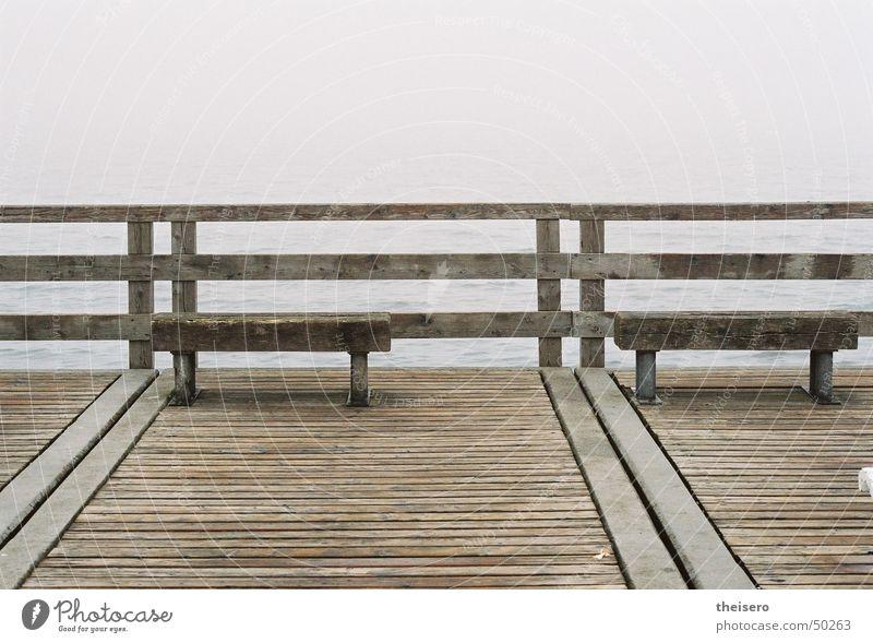 ausblick ins nichts Meer Wasser Horizont Herbst schlechtes Wetter Nebel Küste Ostsee Brücke Sehenswürdigkeit Holz dunkel trist Einsamkeit Seebrücke Bank leer