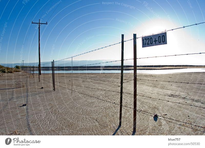 trostlos Wasser Himmel Sonne blau braun Schilder & Markierungen Ziffern & Zahlen Zaun Schlamm Telefonmast Bergkette Stacheldraht Alamogordo New Mexiko