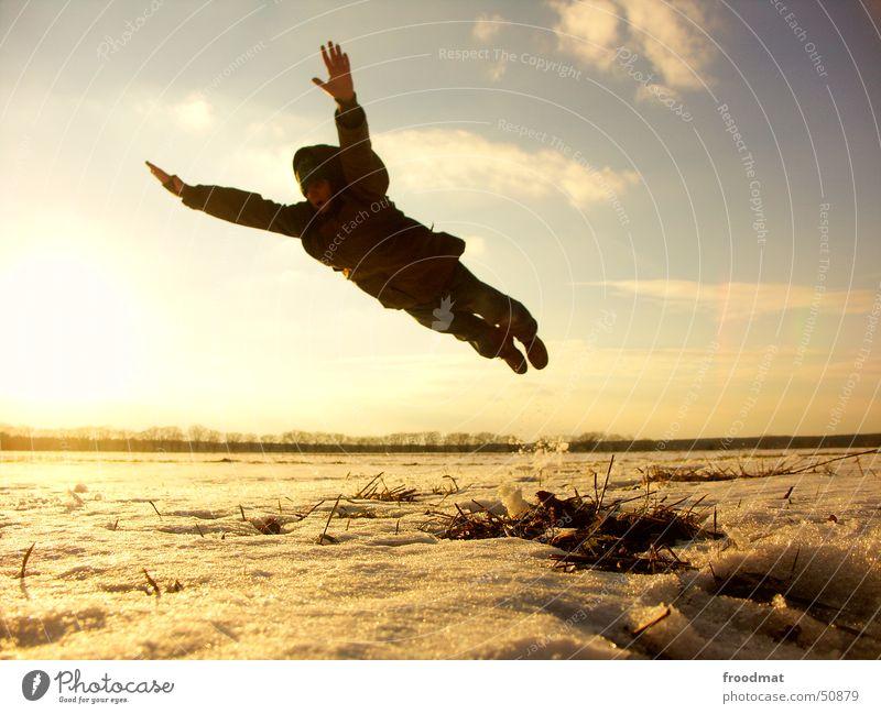 sprung ins kalte wasser Superman springen Winter Sonnenuntergang Gegenlicht gefroren Wiese Wolken Aktion Unbeschwertheit Comic beschwingt lässig frieren