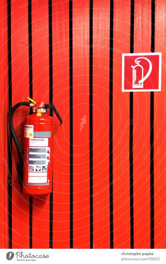 Roter Feuerlöscher an roter Wand Hörsaal Holz Zeichen Hinweisschild Warnschild bedrohlich Sicherheit Schutz gefährlich Häusliches Leben Brandschutz Paneele