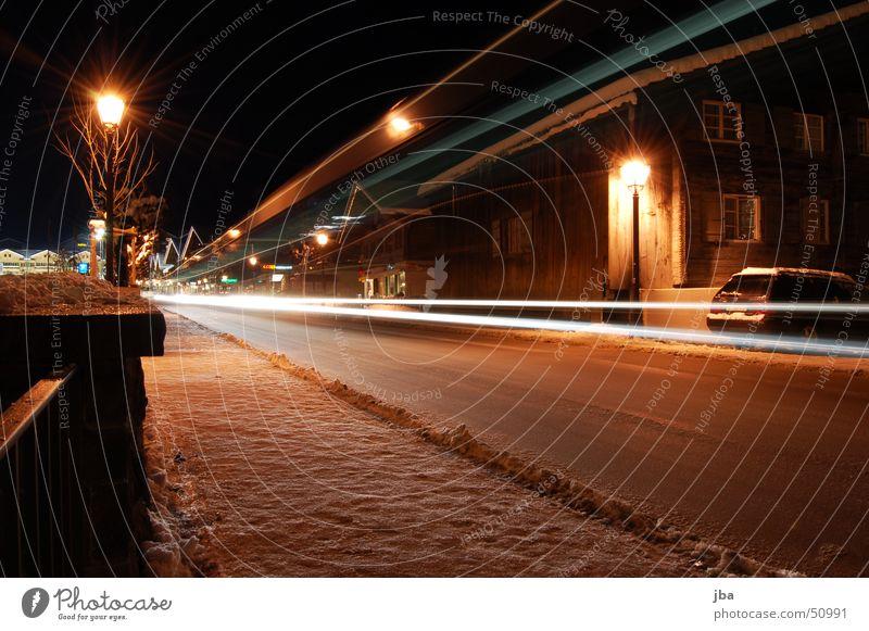 Langzeitbelichtung Licht Postauto Straßenbeleuchtung Bürgersteig Haus Mauer Winter kalt Lichtstreifen Gstaad Saanenland Nacht Schnee