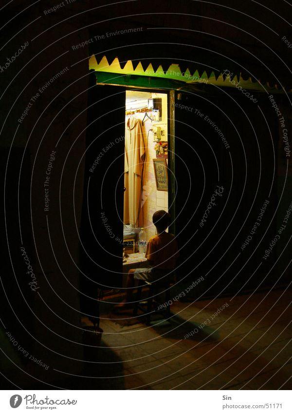 Friseur in Marokko Nacht dunkel Licht Schatten Tür sitzend vor de tür