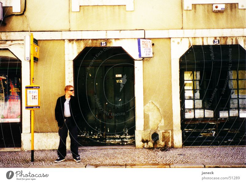 Auf den Straßen von Lissabon Mann Wand Bürgersteig Eingang Sonnenbrille Portugal Straßenbahn
