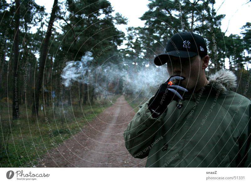 Eine kurze Pause auf dem weg zum Glück Zigarre Zigarette Baseballmütze grün beige Wald Baum schwarz Handschuhe Außenaufnahme Rauchen Gras dunkelgrün Glut