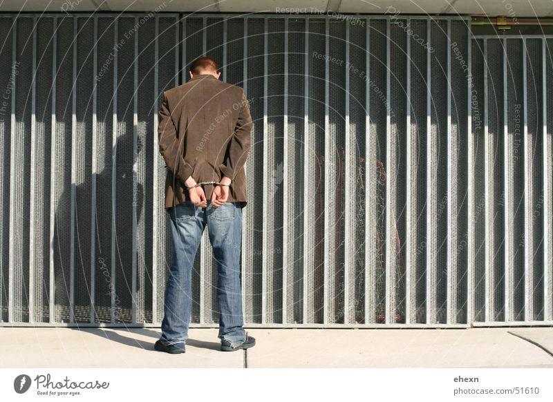 Straftäter Handschellen Krimineller Kriminalität Dieb Wellblech Mann böser junge Schatten man Rücken