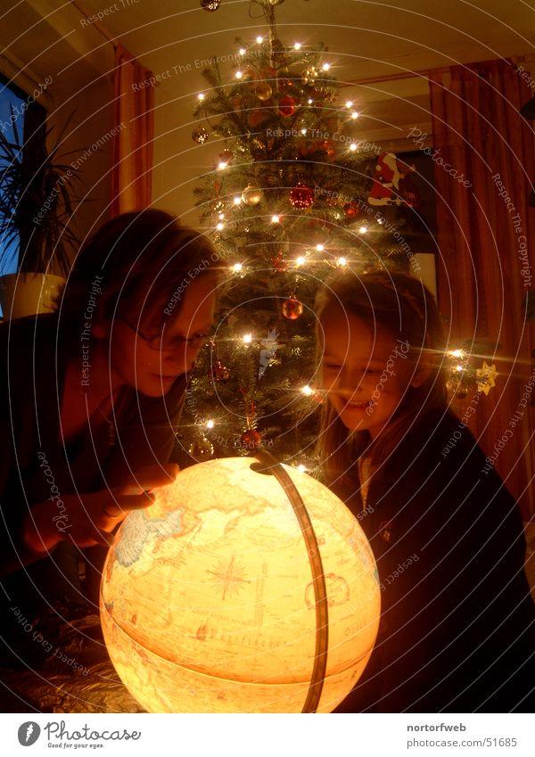 Weihnachtsstimmung spiegelt sich im Lachen eines Kindes Kind Familie & Verwandtschaft Weihnachten & Advent Freude Eltern Licht Stimmung Feste & Feiern Erde Geschenk Mutter Tanne Globus Interpretation Warmes Licht