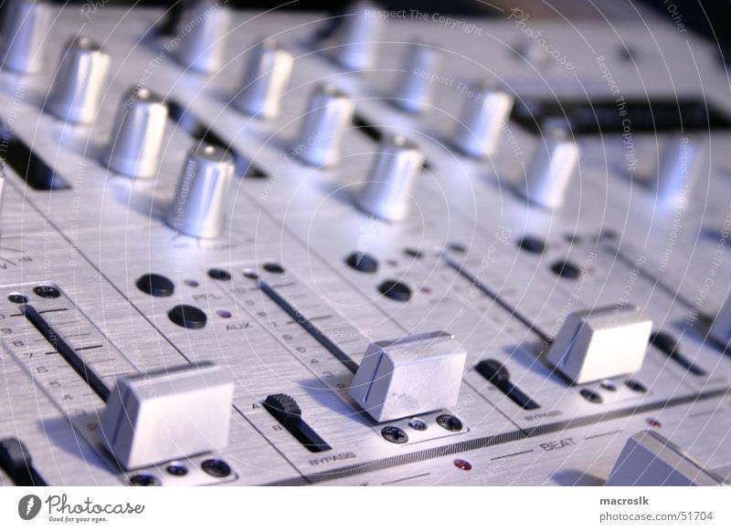 Mischpult in Silber-Blau Musikmischpult Regler schwarz Dreher Veranstaltungstechnik laut ruhig lässig Nachtclub kalt technisch Blauton Nahaufnahme Diskjockey