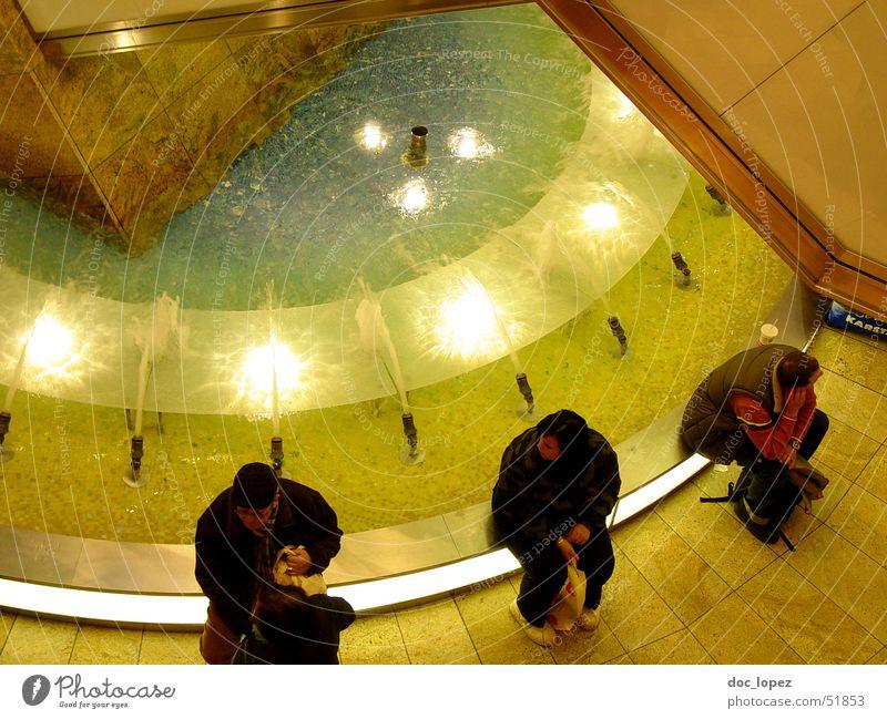 Wasserspeier Mensch Stimmung warten glänzend sitzen Perspektive Brunnen Lichtspiel Einkaufszentrum Springbrunnen