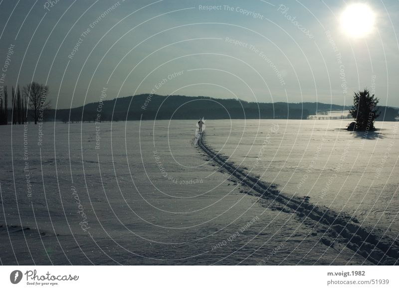 Mann im Schnee - Schneemann? Farbfoto Außenaufnahme Textfreiraum oben Textfreiraum unten Morgen Sonnenlicht Gegenlicht Weitwinkel Ferne Winter Winterurlaub