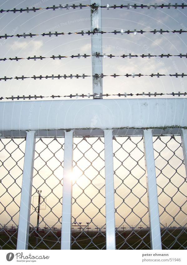 Sun Gate Sonne Lampe Mauer hell geschlossen Sicherheit Schutz Tor Flughafen Grenze Zaun Barriere Draht Geborgenheit Verbote Stab