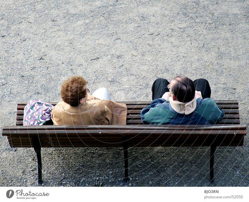 Parkwächter Mann Frau Ehepaar Halskrause rothaarig Holzbank Kies Partner Bank Paar Parkbank Textfreiraum oben Zusammensein zusammengehörig harmonisch