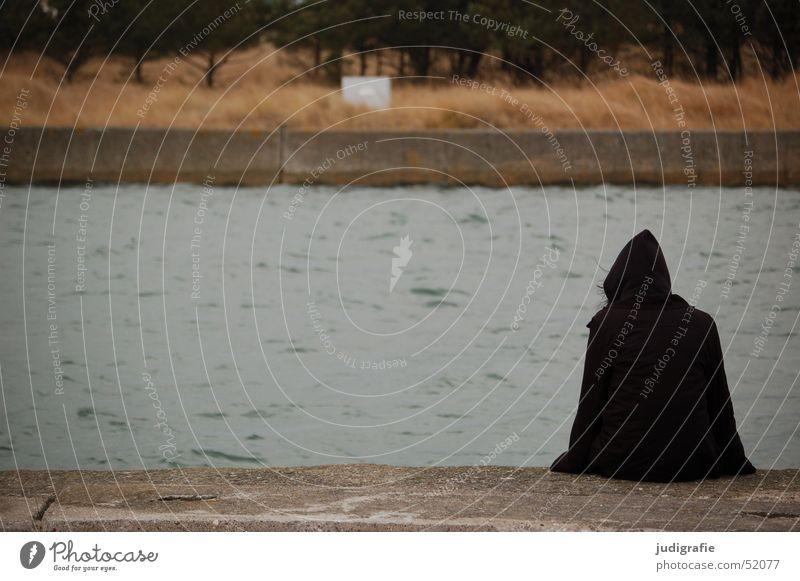Dunkle Gestalt Mensch Natur Wasser Meer Winter schwarz dunkel kalt Tod warten Beton sitzen Hafen geheimnisvoll Jacke Anlegestelle