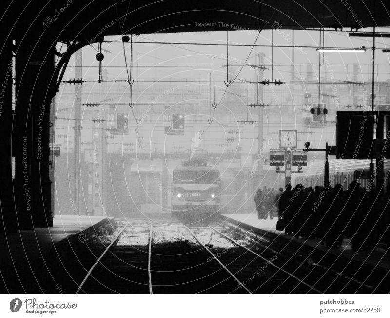 Gare St-Lazare dunkel kalt Paris Verkehr Pendler Eisenbahn Einfahrt Zugeinfahrt kommen Ankunft Fahrzeug Gleise glänzend Bahnsteig Bahnhofsuhr Zeit Schneefall
