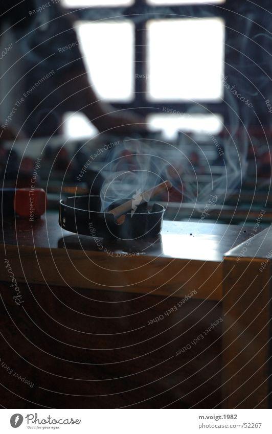 Spielhölle Farbfoto Innenaufnahme Textfreiraum unten Kontrast Gegenlicht Starke Tiefenschärfe Rauchen Spielen Tischfußball Aschenbecher Zigarette authentisch