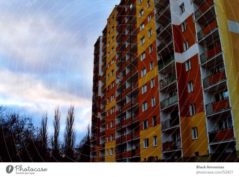 Farbige Tristesse Gebäude Plattenbau Balkon gelb rot Wolken Baum Macht orange Himmel bedecken groß Perspektive