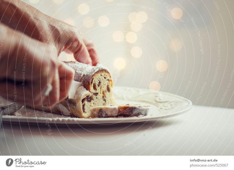Stollen Lebensmittel Teigwaren Backwaren Kuchen Dessert Christstollen gold Weihnachten & Advent Messer schneiden Rosinen Hand festhalten Farbfoto Innenaufnahme