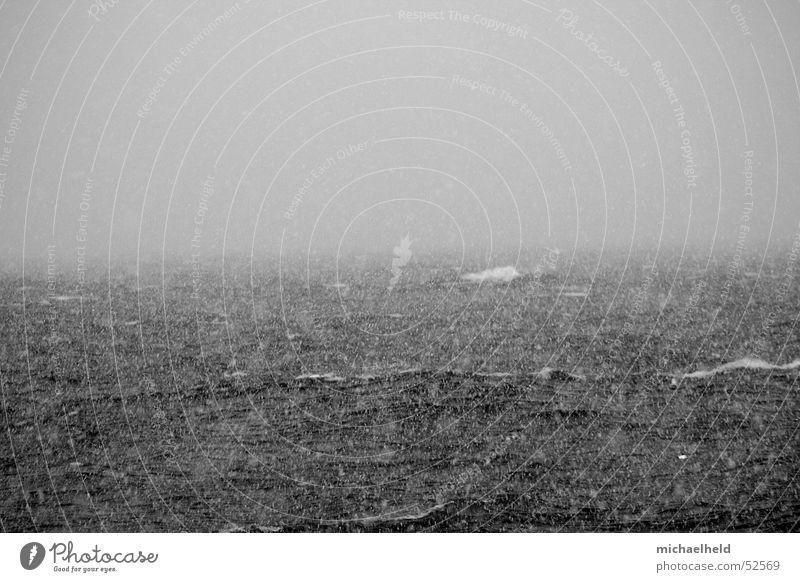 Ungewissheit Meer schwarz weiß Wellen Schaum schlechtes Wetter Nebel trüb Horizont grau ungewiss gefährlich gewagt Schnee schlechte sicht Schwarzweißfoto