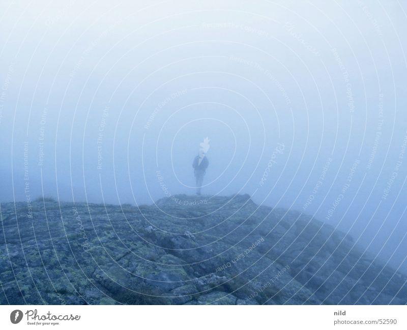 Bergwelt ohne Berg Mann blau ruhig Einsamkeit Herbst grau Nebel Felsen Perspektive trist Flucht mystisch Bergsteigen Rucksack Klettern orientierungslos