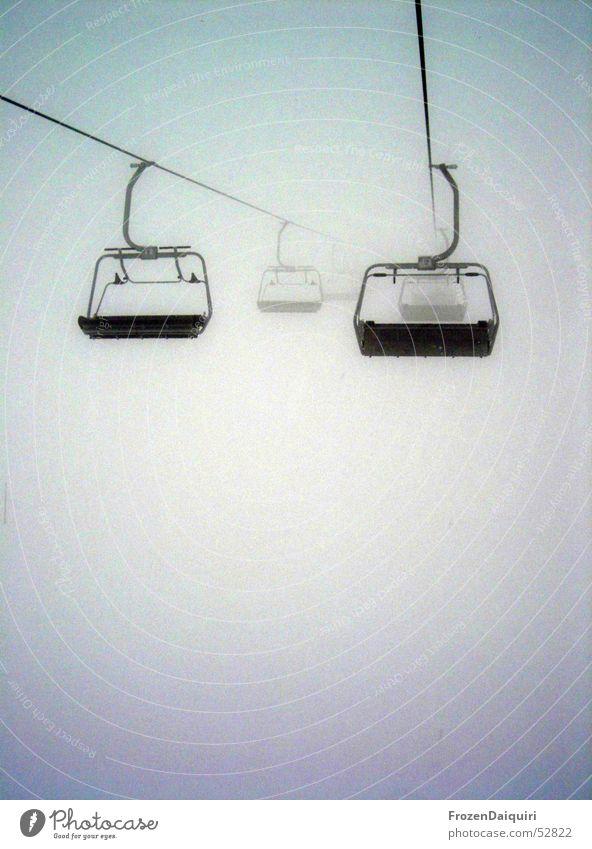 Sessellift ins Nichts Nebel dunkel ungewiss Sesselbahn hängen Abhängigkeit Westendorf Bundesland Tirol Winter frieren kalt feucht Drahtseil hell Kontrast Angst