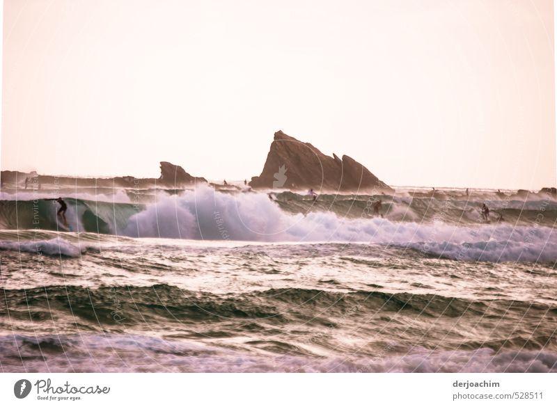 Lebensfreude beim Surfen im Meer mit Brandung. Im Hintergrund sind Felsen zu sehen. Freude sportlich Wohlgefühl Freizeit & Hobby Wellen Wassersport