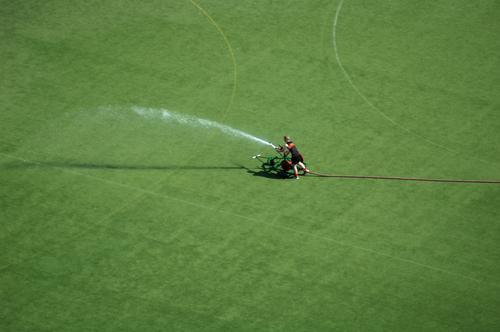 Explosiv Feldhockey sprengen gießen Tennis Helfer Mann nass grün Wasserfontäne Gras Schlauch Arbeit & Erwerbstätigkeit Baseball liquide Spray Sommer Rasen