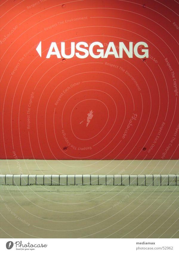 Ausgang rot Wand Beton Flucht Wegweiser Parkhaus Bordsteinkante Hochformat