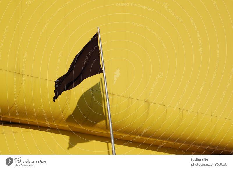 Schwarze Fahne mit Schatten vor gelbem Gebäude schwarz Licht Hannover Fahnenmast Pavillon Litauischer Pavillon modern Weltausstellung Architektur