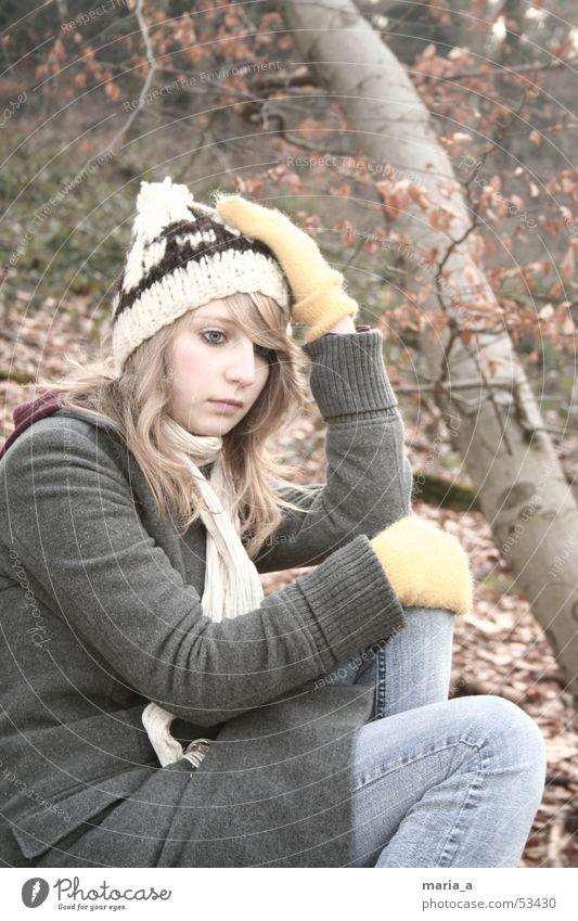 im Wald Frau Baum Blatt Handschuhe Mantel Mütze Schal Herbst Winter kalt Denken blond Baumstamm Jeanshose Tuch sitzen Mensch