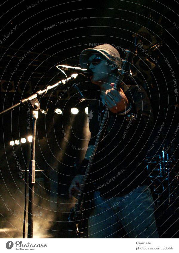 o.T. Japaner Bühne Mikrofon Licht Mütze Mann dunkel Rocker singen Lied Rockmusik stage Musik Gitarre Kontrabass light