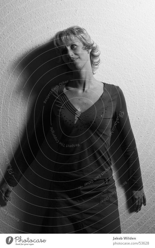 Schatten Frau blond verträumt Wand weiß dunkel geheimnisvoll Linie Schwarzweißfoto Kontrast anlehnen